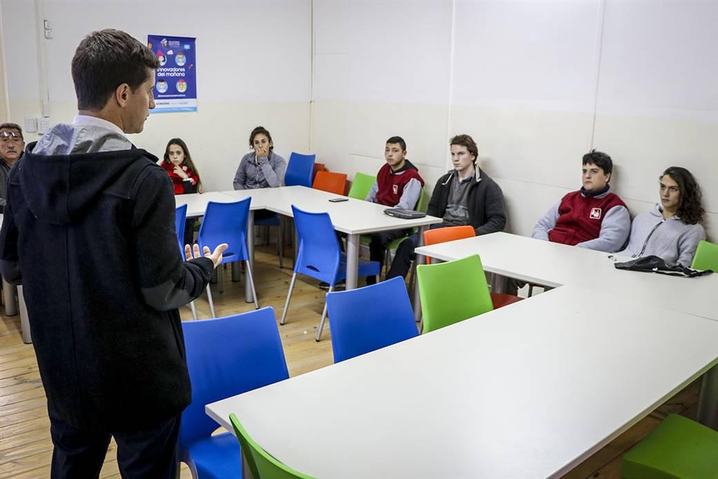 En la imagen se observa al secretario de modernización del municipio, Maximiliano Steffan, dialogando con los alumnos que desarrollan la aplicación.