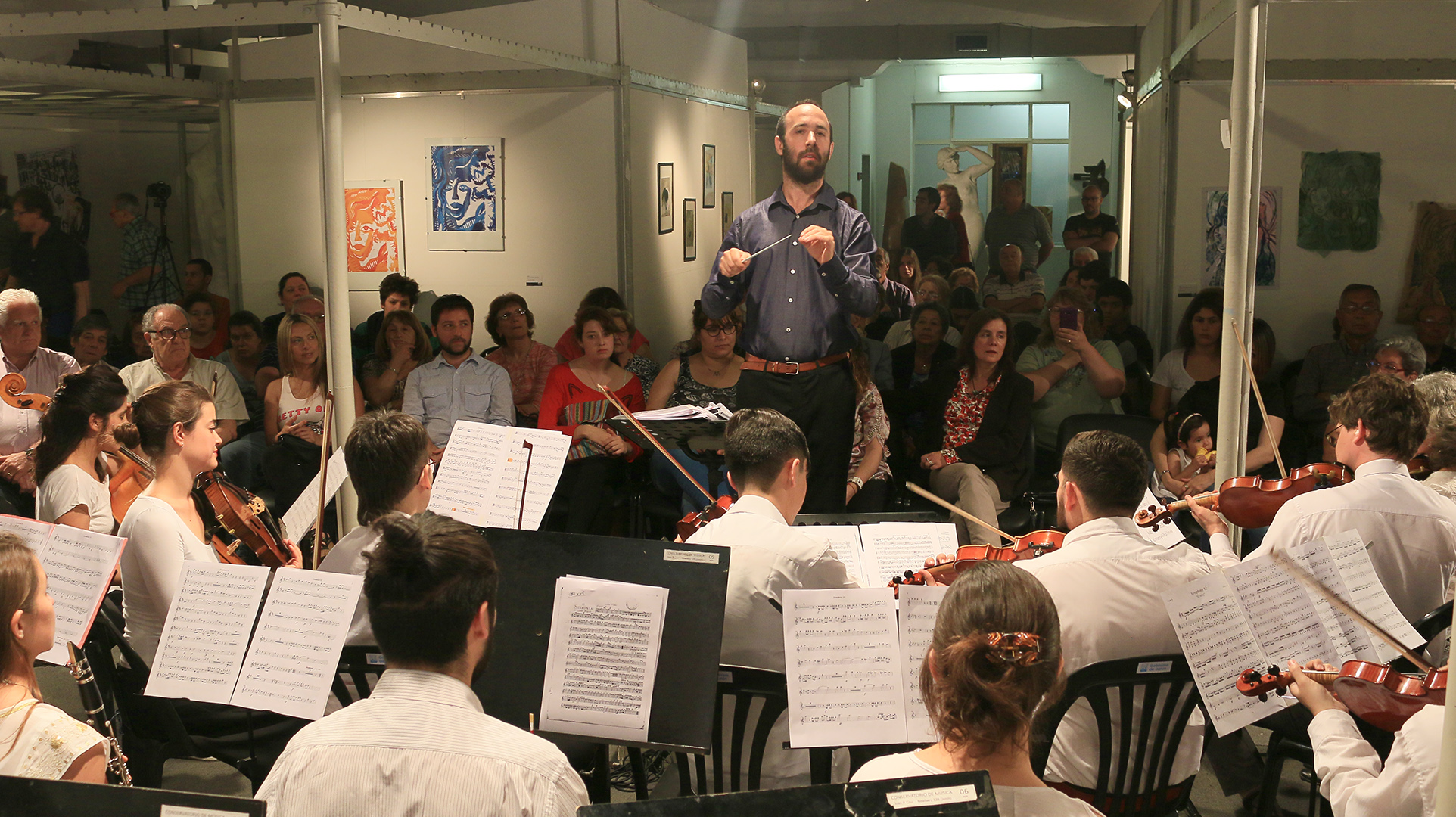 En la imagen se observa a integrantes de la orquesta académica y del público en plena presentación.
