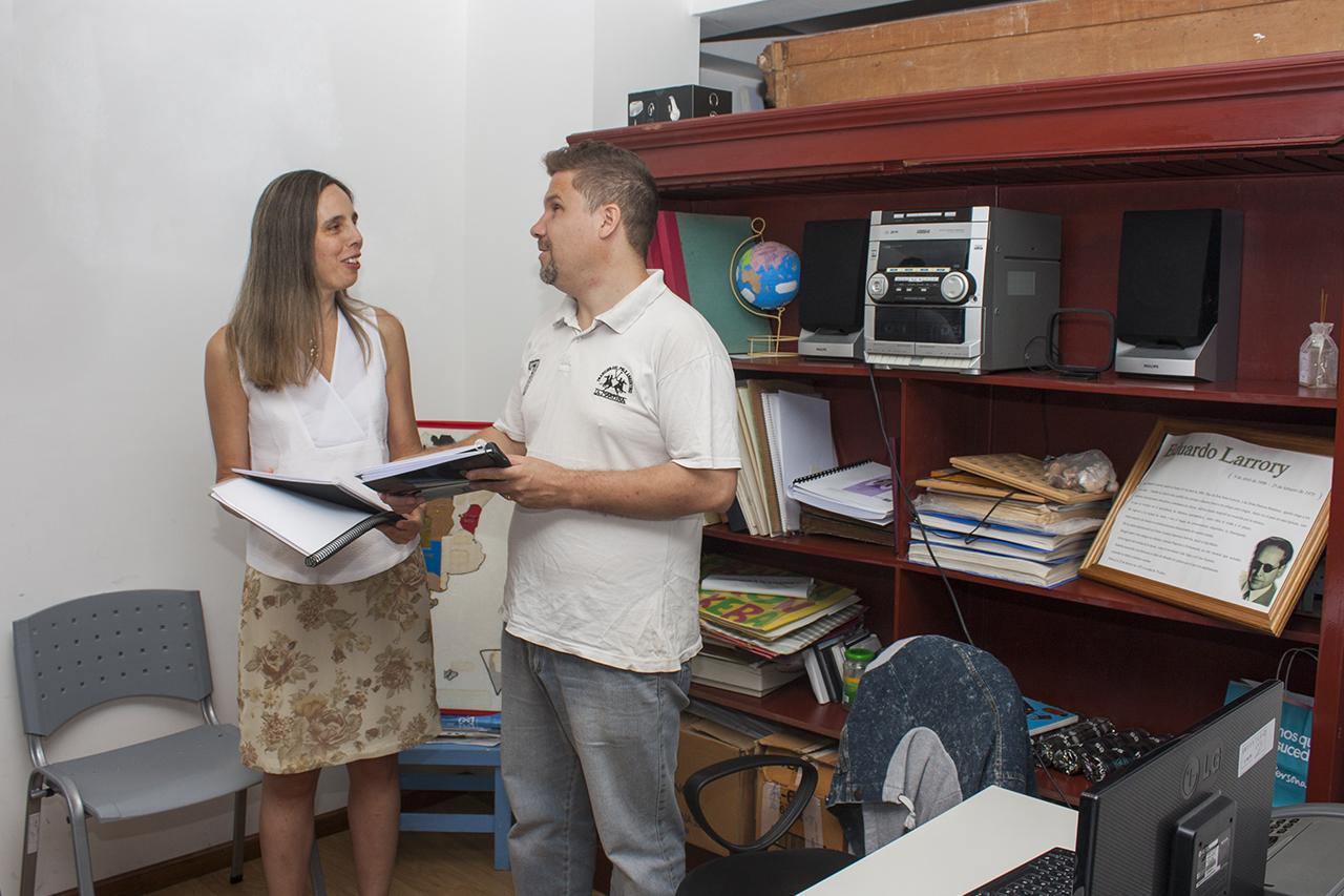 En la imagen se observa a la titular de la dirección de personas con discapacidad, Karina Sánchez, haciendo entrega al bibliotecario Iván Guajardo, de los cuentos infantiles.