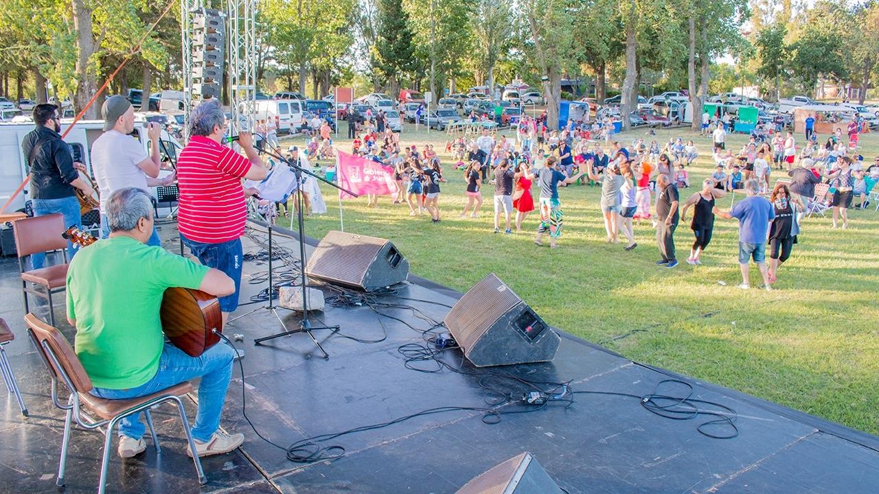 En la imagen se observa a músicos actuando mientras el público acompaña bailando.