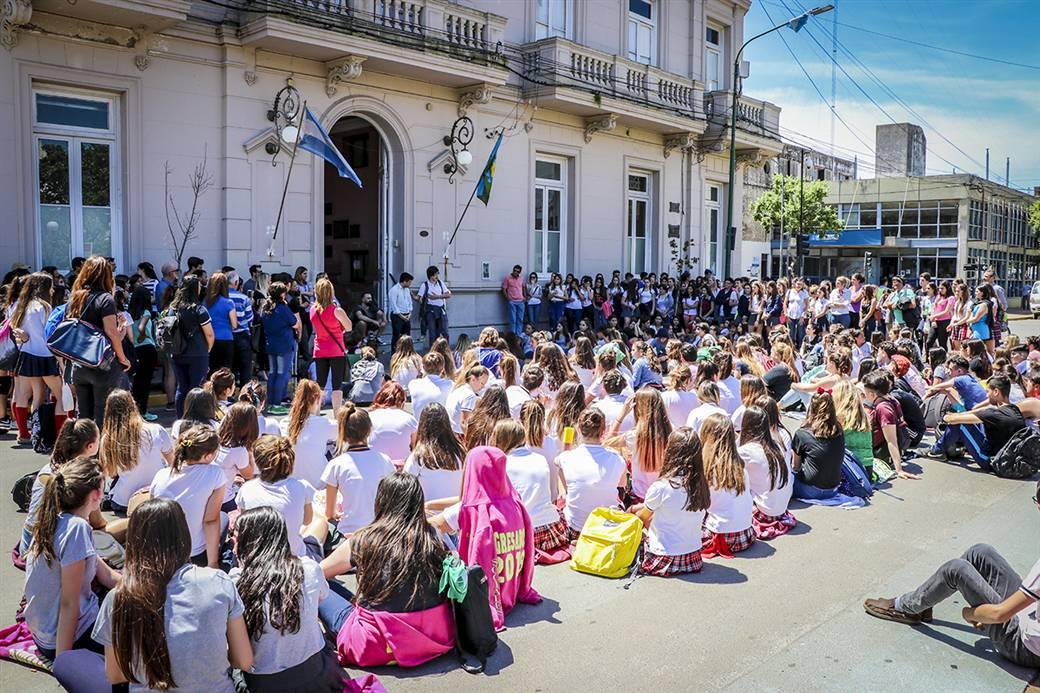 En la imagen, se observa a los jóvenes sentados sobre la calle frente al palacio municipal.