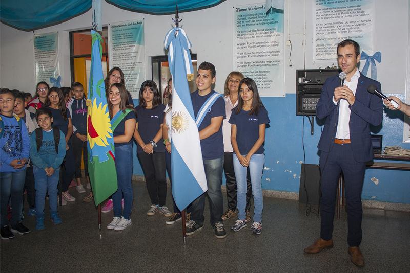En la imagen se observa al Intendente Pablo Petrecca haciendo uso de la palabra frente a los alumnos de la escuela secundaria 18, lo hace acompañado de los abanderados de dicha institución.