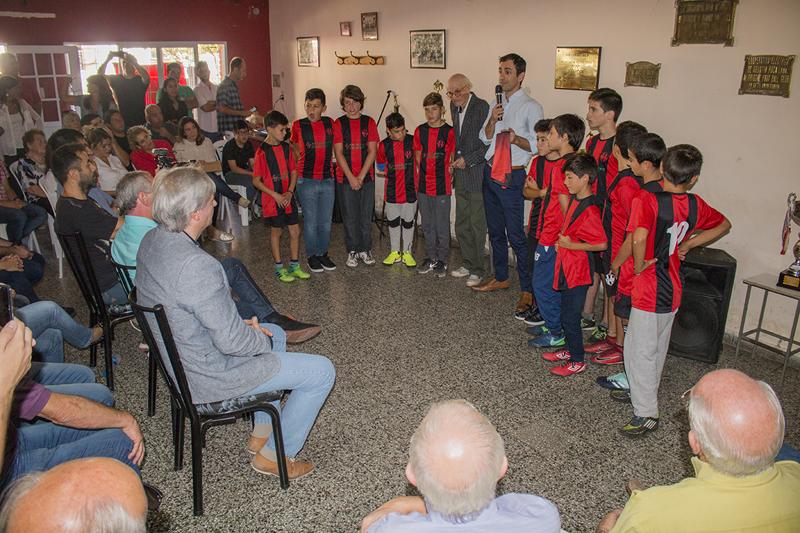En la imagen se observa al Intendente Pablo Petrecca haciendo uso de la palabra en el acto por los 100 años del club y rodeado de chicos de las inferiores.