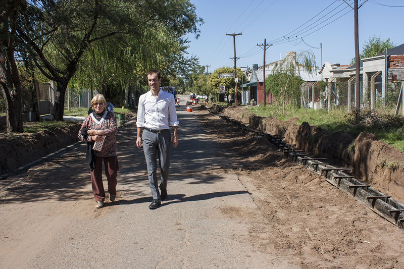 En la imagen se observa al Intendente Pablo Petrecca recorriendo la obra de calle Lonegro junto a una vecina.