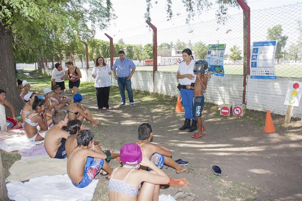 En la imagen se observa a la oficial de la policía local brindando la charla a los chicos que asisten a la escuela de verano.